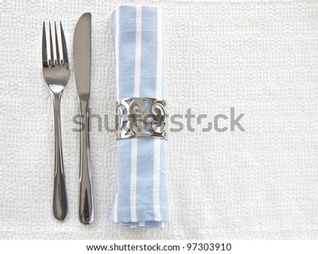 Table setting with blue and white striped napkin and knife and fork with space for text