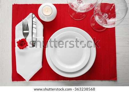 Table setting with dishes and  cutlery on red background - stock photo