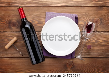 Table setting with empty plate, wine glass and red wine bottle. View from above over rustic wooden table background - stock photo