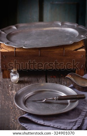 Table Setting with Empty vintage metal plate and dish with fork, napkin and salt, prepare for rustic dinner. Over old wooden table. - stock photo