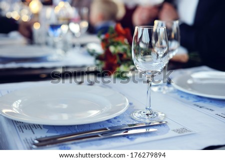 Table setting with fork, knife, plates and glass - stock photo