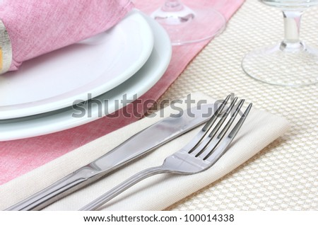 Table setting with fork, knife, plates, and napkin - stock photo