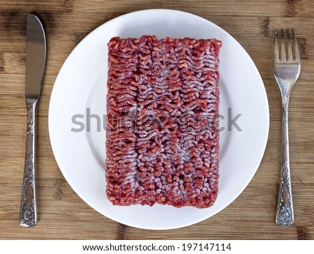 Table setting with frozen ground lean beef - stock photo