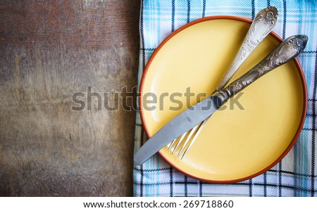 Table Setting with napkin and silverware on wooden table - stock photo