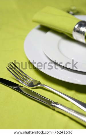 table setting with plates, napkin, silverware and glass on apple green table cloth - stock photo