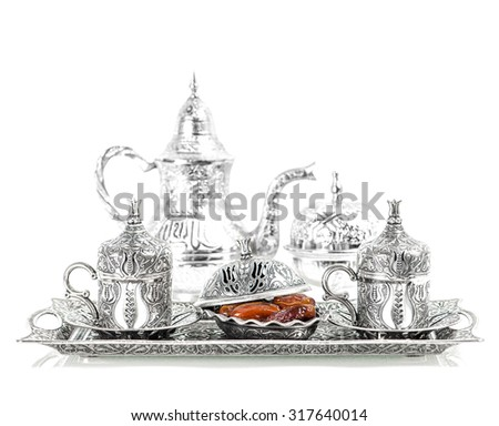 Table setting with silver tableware and dates. Oriental hospitality concept with tea or coffee cups. High key picture - stock photo