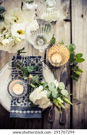 Table setting with white flowers, candles and glasses on old vintage rustic wooden table. Vintage summer wedding table decoration, top view. - stock photo