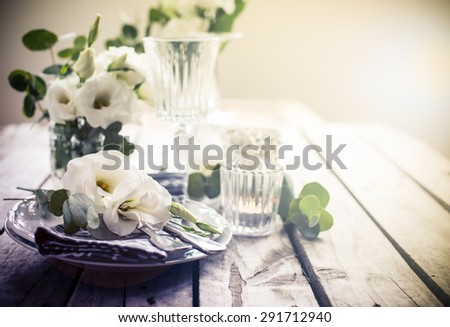Table setting with white flowers, candles and glasses on old vintage rustic wooden table. Vintage summer wedding table decoration. - stock photo