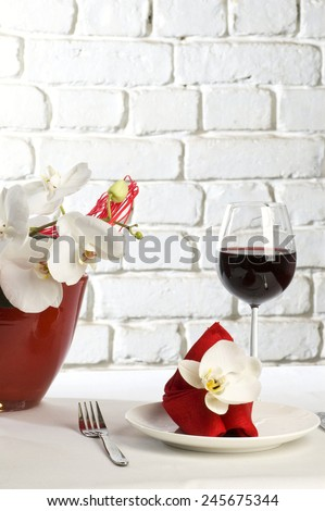 Table setting with white orchid flowers on white tablecloth on brick wall background - stock photo