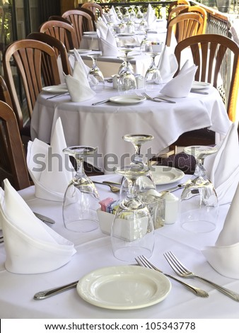 Table settings on white linen at outdoor restaurant - stock photo