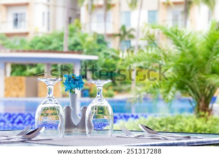 table setup in outdoor cafe, small restaurant at hotel poolside, summer vacations, meal time - stock photo