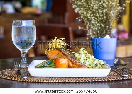 table setup in outdoor cafe, small restaurant in a hotel, summer vacations, meal time, grilled salmon with pasta and vegetables - stock photo