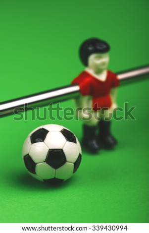 Table soccer player figurine with football, selective focus