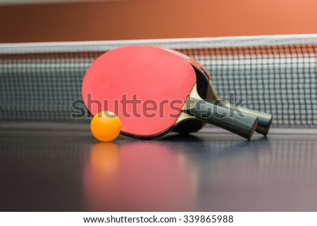 table tennis racket with orange ball on black table - stock photo