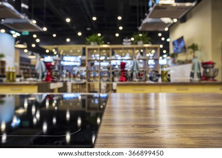 Table top with an oven in the blurry background of a kitchen - stock photo