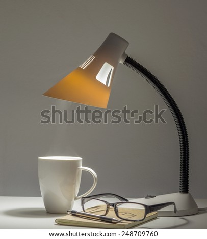 Table type lamp for night reading and working with coffee cup and eyeglasses - stock photo