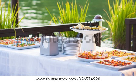 Table with a lot of food for stand-up meal outdoor - stock photo