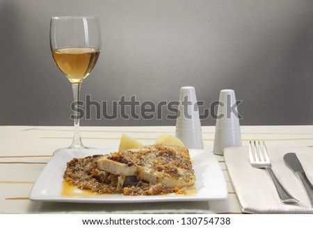 table with a plate of food, wine glass and cutlery