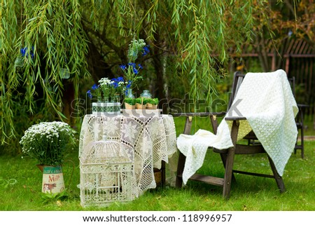 table with a tablecloth and chairs in the garden