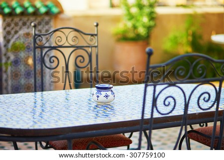 Table with blue ceramic ash tray and yellow chairs in cozy Moroccan restaurant in Essaouira, Morocco - stock photo