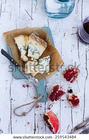 Table with blue cheese and slices of pomegranate over on vintage white wooden surface. Natural and healthy food concept. Fresh ingredients on a wooden table. Rustic style. Top view - stock photo