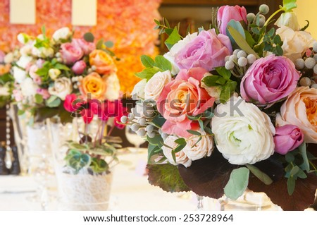 Table with bouquets of roses and cyclamen plants setting for wedding - stock photo