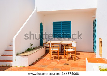 Table with chairs on patio of holiday house in Alvor town, Algarve region, Portugal - stock photo