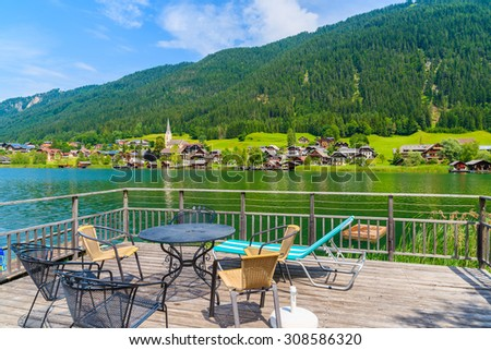 Table with chairs on wooden deck and view of green water Weissensee lake in summer landscape of Alps mountains, Austria - stock photo