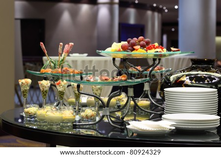 Table with cold snacks and fruits on stand and tableware on luxury stand-up party - stock photo