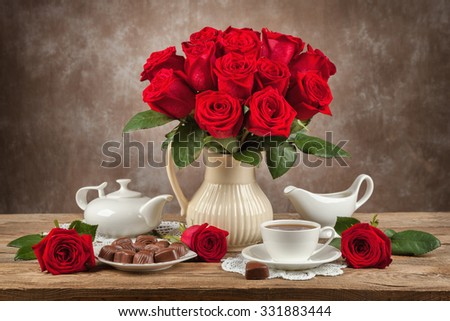 table with cups of tea, chocolates and a bouquet of roses - stock photo
