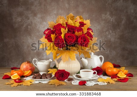 table with cups of tea, chocolates and a bouquet of roses and aunumn leaf. - stock photo