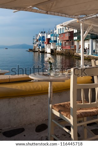 Table with flowers in cafe at Little Venice at sunset. Mykonos. Greece. - stock photo