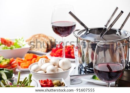 table with fondue set and ingredients - stock photo