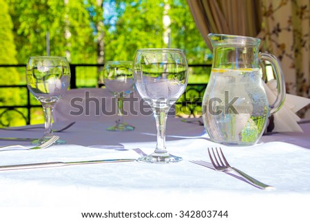 Table with glasses and white tablecloth in bower. Photo of summer hotel complex.
