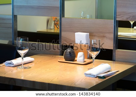 Table with glasses in the cafe with cozy interior. - stock photo