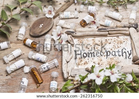 Table with handwritten text  Homeopathy, spoon homeopathy globules and flowers - stock photo