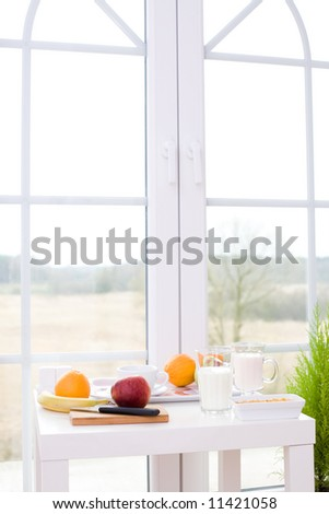 Table with healthy snacks / fruits, joghurt, cereal - stock photo