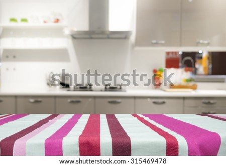 Table with linen tablecloth for present product on kitchen blur background - stock photo