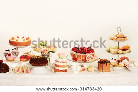 Table with loads of cupcakes and cakepops and birthday cakes - stock photo