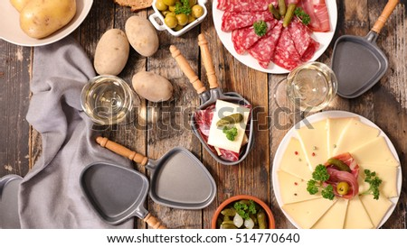 table with raclette cheese, meat and potato