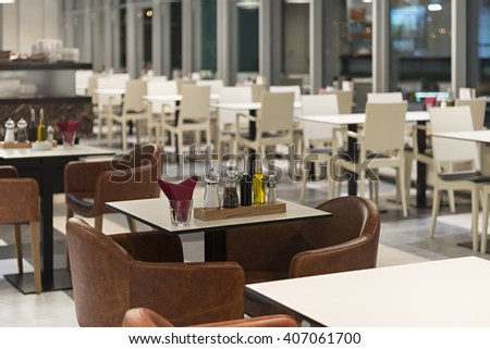 Table with salt and pepper cruet set in empty restaurant