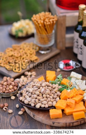 table with snacks, cheese, pistachios, hazelnuts, beer - stock photo