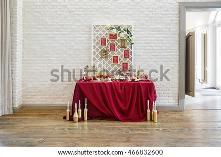 Table with sweets covered with red cloth and surrounded with golden bottles stand behind a white brick wall