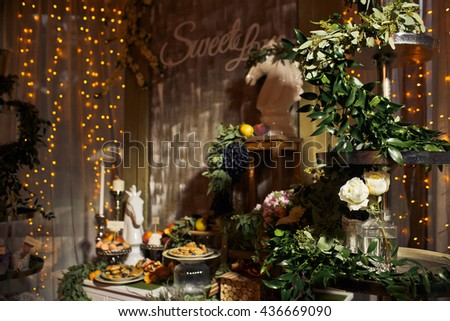 Table with sweets decorated with greenery