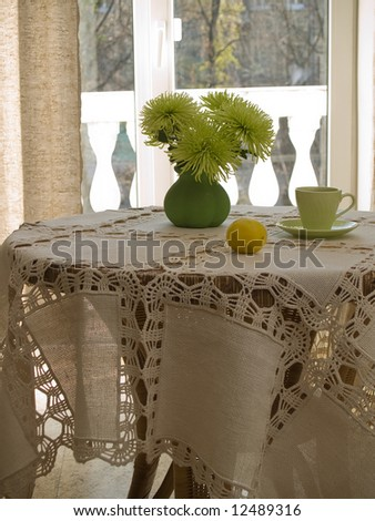 Table with table-cloth in interior in sunny day