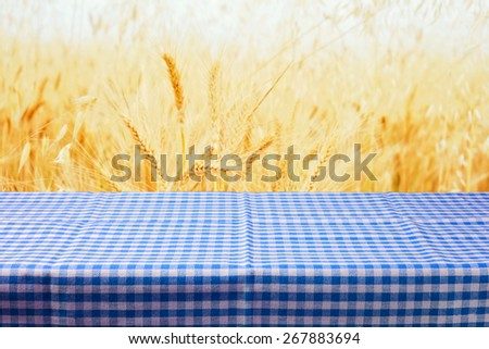 Table with tablecloth over wheat field background - stock photo