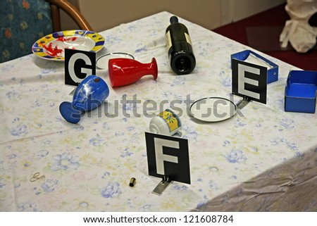 table with things overturned during a fight and the forensic dentification - stock photo
