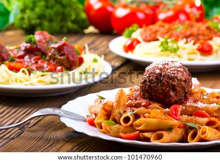 Table with tree plates of Italian pasta and tomato sauce