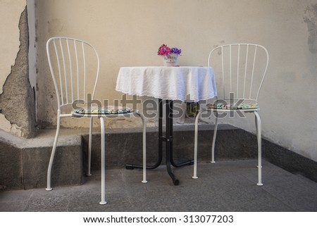 table with two chairs on stone stairs