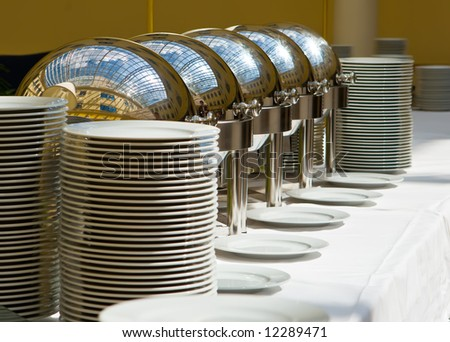 Table with utensils and mirror boilers for meal - stock photo